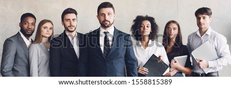 Business team headed with boss, posing to camera over grey wall in office #1558815389