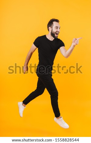 Full length image of handsome man in basic clothes walking and pointing finger aside isolated over yellow background #1558828544