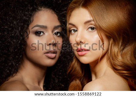 Multi-ethnic beauty. Caucasian and African. Different ethnicity women on black background. Beautiful vogue girls. #1558869122