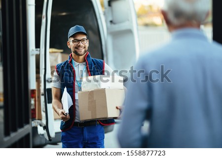Happy deliverer carrying packages while making home delivery to his customer.  Royalty-Free Stock Photo #1558877723
