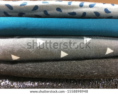 Preparation for sewing or crafting. Folded fabrics in stripes, solids, dots patterns. Textiles prepared for garment construction.  #1558898948