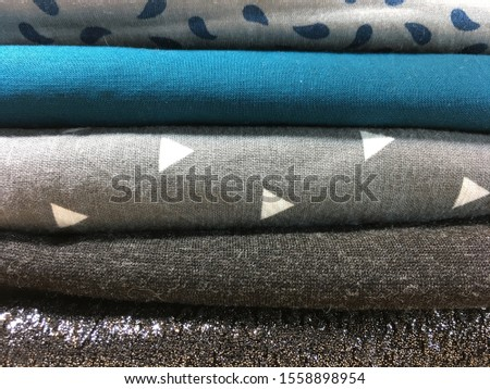 Preparation for sewing or crafting. Folded fabrics in stripes, solids, dots patterns. Textiles prepared for garment construction.  #1558898954