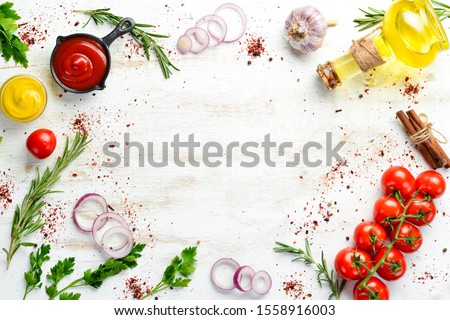 White wooden background of cooking. Spices and vegetables. Top view. Free space for your text. #1558916003