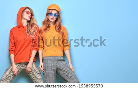 Two easy-going happy hipster Woman smiling, Stylish fashion orange colored outfit. Beautiful Girl in Trendy sunglasses, sweatshirt, cap. Joyful sister, friend. Creative fashionable friendship concept #1558955570