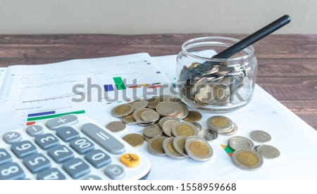 Line graphs, pie graphs, and graphs of various colors printed on white paper Placed on a wooden patterned work desk Complete with a calculator and a pile of Thai baht coins #1558959668