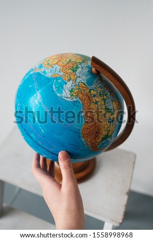 Kazan, Russia, February 29, 2016:Female hand by rotating and touching a world globe isolated on a white background. Education, science, exploration concept. Copy space #1558998968