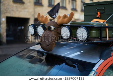 Moose figure at teh roof of car Royalty-Free Stock Photo #1559009135