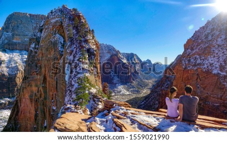 COPY SPACE, LENS FLARE: Young couple sits atop Angel's Landing and observes the breathtaking canyon in Utah. Tourist observe the valley and red sandstone mountains after a successful hike in Zion Park #1559021990