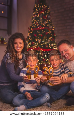 Parents celebrating Christmas with their children, sitting by Christmas tree, holding cupcakes with candles shaped as numbers 2020, representing the upcoming New Year #1559024183