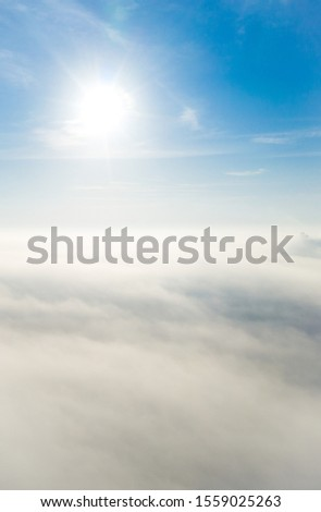 Aerial photo above the fog or white clouds with shining sun. Beautiful sunrise cloudy sky from aerial view. Above clouds from airplane window or drone. #1559025263