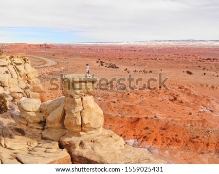 DRONE: Woman standing on top of a sandstone formation taking photos of he beautiful canyon and orange hued desert. Female photographer taking landscape photos from a boulder overlooking wilderness. #1559025431
