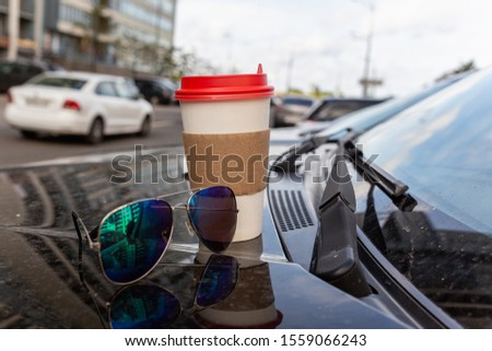 White paper Cup of coffee with the red cover on the hood of the car. Paper Cup with hot tea on the hood of the SUV, closeup on the background of the windshield #1559066243