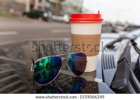 White paper Cup of coffee with the red cover on the hood of the car. Paper Cup with hot tea on the hood of the SUV, closeup on the background of the windshield #1559066249