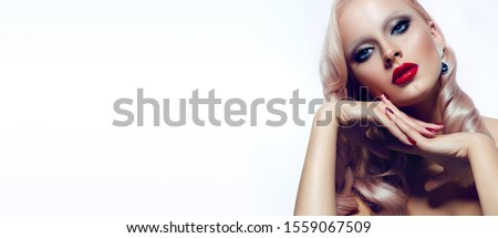 Beautiful spectacular blonde with bright makeup and red lips, with a pink tint of hair with a retro hairstyle, sits in the studio on a white background in an elegant pose and holds her hands with red  #1559067509