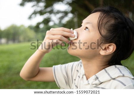 Sick asian child girl using tissue paper for stop bleeding from the nose,female teenage with nosebleed or epistaxis suffer from allergic rhinitis,respiratory or nose injury, bleeding from an accident #1559072021