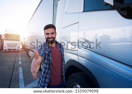 Truck drivers job openings. Middle aged professional trucker driver standing in front of his truck and giving shaking to new recruits. Truck driving careers. #1559079098