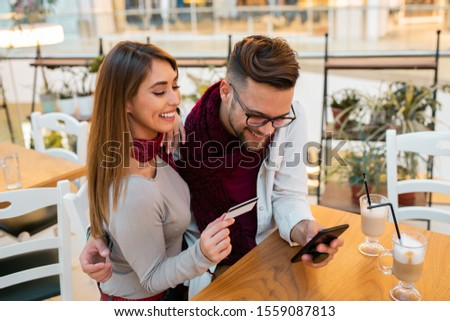 A couple purchasing something on the phone, paying by card. They trust each other, they trust their favorite online store, they trust e-purchases. #1559087813