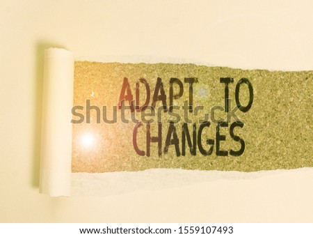 Conceptual hand writing showing Adapt To Changes. Business photo showcasing Embrace new opportunities Growth Adaptation progress Cardboard which is torn placed above a wooden classic table. #1559107493
