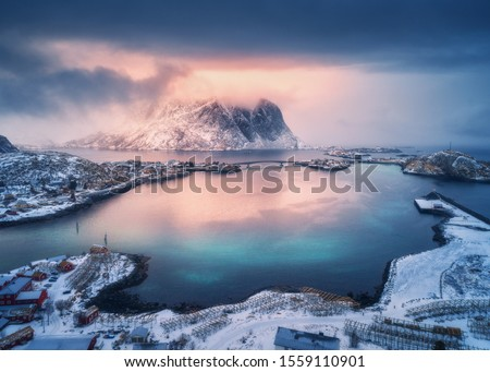 Aerial view of snowy mountain, village on sea coast, orange sky at sunset in winter. Top view of Reine, Lofoten islands, Norway. Moody landscape with high rocks, houses, rorbu, reflection in water #1559110901