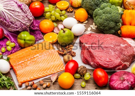 Trending paleo/pegan diet. Healthy balanced food concept. Set of fresh products, raw meat, salmon, vegetables and fruits. Old wooden boards background #1559116064