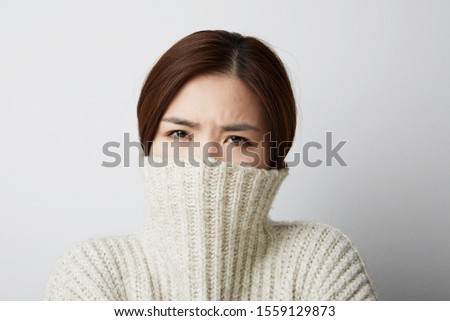 Close-up of Chinese woman posing on the white background. Isolated. #1559129873