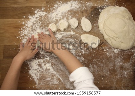 child sculpts flour products from dough on a wooden table, sprinkled with flour, close-up, selective focus, home cooking concept, copy space #1559158577