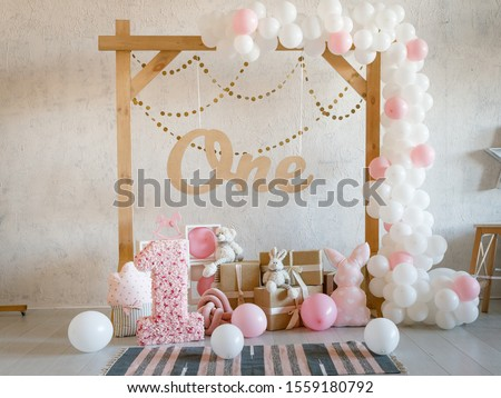Birthday decorations with wooden arch, gifts, toys, balloons, garland and figure 1 for little baby party on a white wall background. Royalty-Free Stock Photo #1559180792
