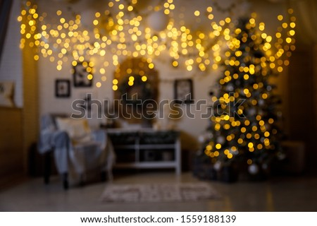 Christmas and New Year interior - blur background: fireplace, lamps, green Christmas tree, brown leather sofa, gifts, candles, moose rocking chair. #1559188139