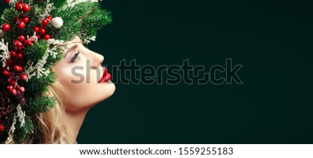 Christmas winter beauty girl. Beautiful happy young woman with a Christmas pine wreath on her head, decorated with Christmas balls, berries and snowflakes.  #1559255183