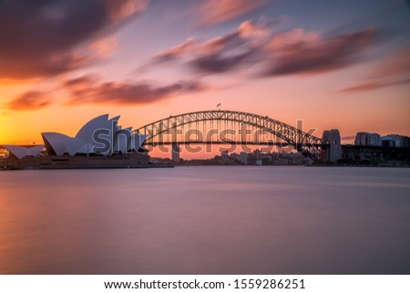 A beautiful shot of the Sydney harbor bridge with a light pink and blue sky in the background at sunset Royalty-Free Stock Photo #1559286251