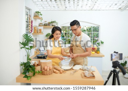 Young asian couple cooking together and recording live video for vlog and social media with professional camera #1559287946