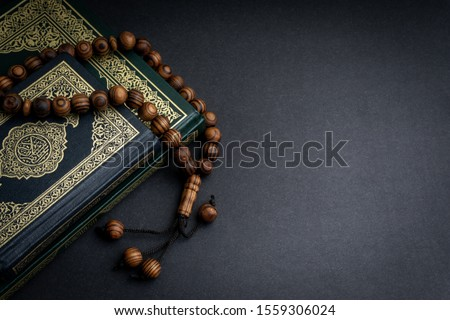 Holy Al Quran with written arabic calligraphy meaning of Al Quran and rosary beads or tasbih on black background. Copy space and crop fragment #1559306024