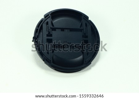 Backside of plastic lens cover isolated on the white background. Black front lens cap. Using for protect the damage of lens' surface. Inside of a lens cap.  #1559332646
