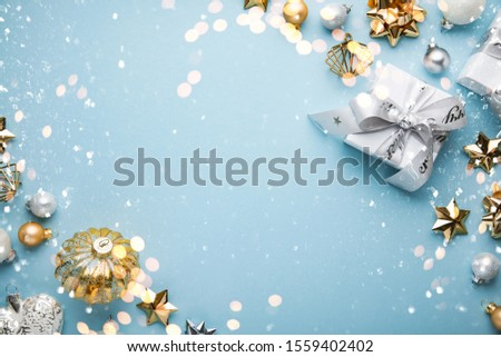 Merry Christmas and Happy Holidays greeting card, frame, banner. New Year. Noel. Christmas white, silver and golden ornaments and gifts on blue background top view. Winter xmas holiday theme. Flat lay Royalty-Free Stock Photo #1559402402
