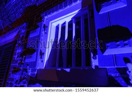 Old-fashioned window with strong metal bars at night, illuminated in blue #1559452637