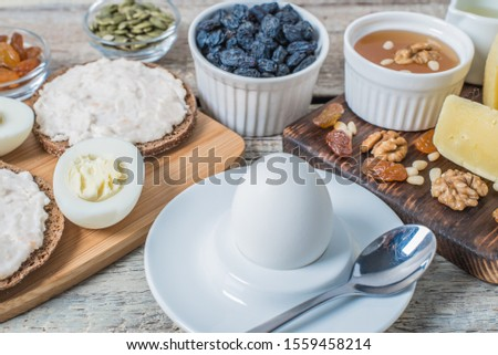 Boiled egg in egg cup and sandwich with cheese with slice egg, raisin, honey, parmesan, nut and pumpkin seed. Healthy breakfast on a wooden table #1559458214