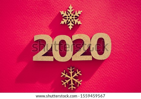 2020 winter holiday red background with hand made wooden figures and snow flakes shot in flat lay style from above.Christmas Eve and Happy New Year celebration party poster
