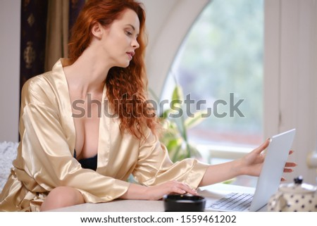 Pretty beautiful woman working on a laptop at the window in the house #1559461202