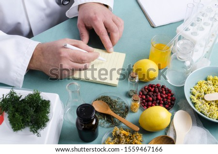 Concept of natural medicine. Doctor sitting st the table and making a prescription. Natural ingredients for health care on the blue table.Herbs, lemons, berries and other different components #1559467166