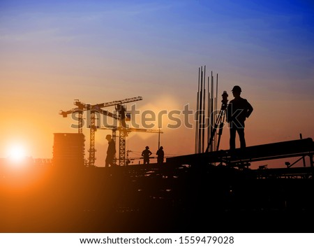 Silhouette of Survey Engineer and construction team working at site over blurred  industry background with Light fair Film Grain effect.Create from multiple reference images together #1559479028