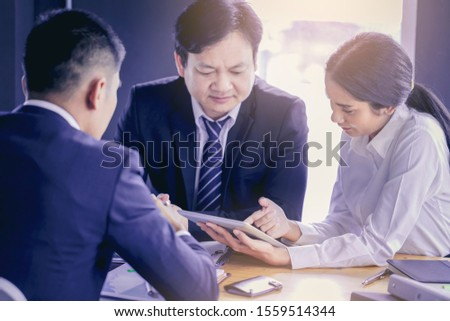 Crop image of young attractive businesswoman working with touchpad has been guided and consulting by colleagues #1559514344
