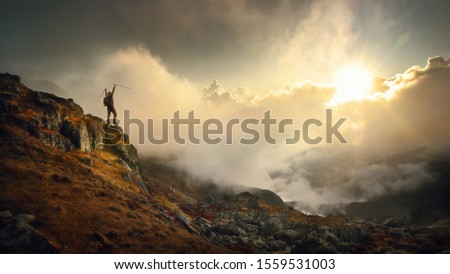 Hiker in mountains with a backpack and trekking poles rejoices at the top during a beautiful sunset in the Himalayas. Nepal.Travel and adventure sport lifestyle concept. #1559531003