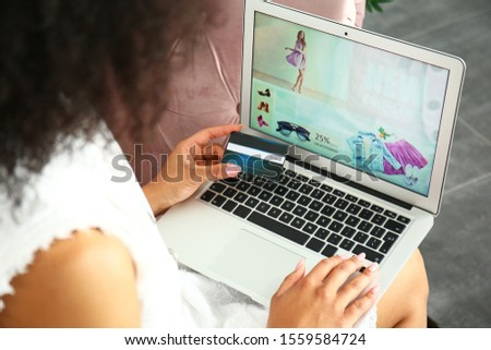 Beautiful African-American woman using laptop for online shopping at home #1559584724
