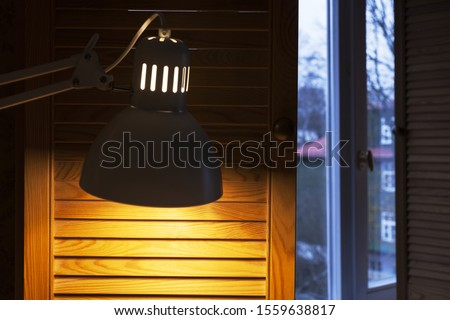 Desk lamp casting warm light on brown wooden shutter indoor in morning /at day, as natural daylight outside looks bluish. Color temperature concept.
