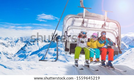 Happy family on ski lift chair enjoying winter ski vacations in mountains  Playing with snow and sun in high mountains. Winter holidays. #1559645219