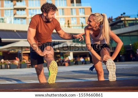 Modern couple doing exercise in urban area. #1559660861
