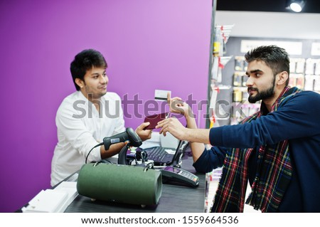 Indian man customer buyer pay for his new smartphone for seller by credit card at mobile phone store. South asian peoples and technologies concept. Cellphone shop. Royalty-Free Stock Photo #1559664536