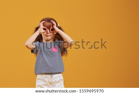 Cute little girl in casual clothes have fun in the studio against yellow background. #1559695970