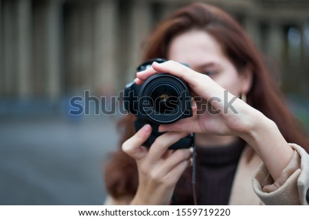 Selective focus on lens. Beautiful stylish fashionable girl holds camera in hands and takes pictures. Woman photographer with long dark hair in city, urban shoot, vertical. unrecognizable person, #1559719220