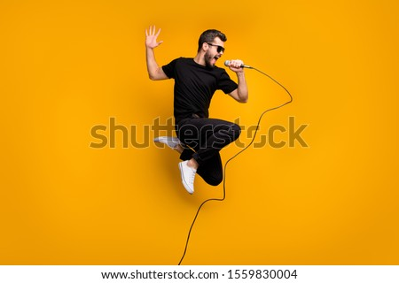 Full body profile photo of crazy hipster guy jumping high holding microphone music lover singing favorite song wear sun specs black t-shirt pants isolated yellow color background #1559830004